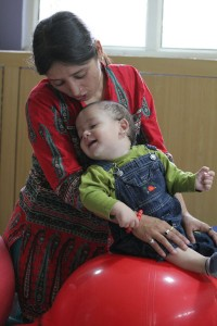 Teacher with child in blue jeans on a red ball