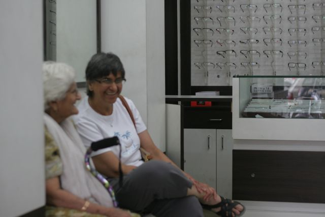 Woman sits with her mother in a spectacles shop