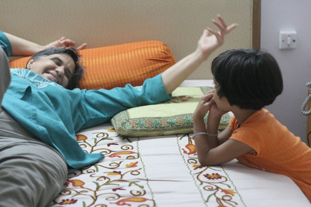 Woman on bed in animated conversation with little girl on the side.