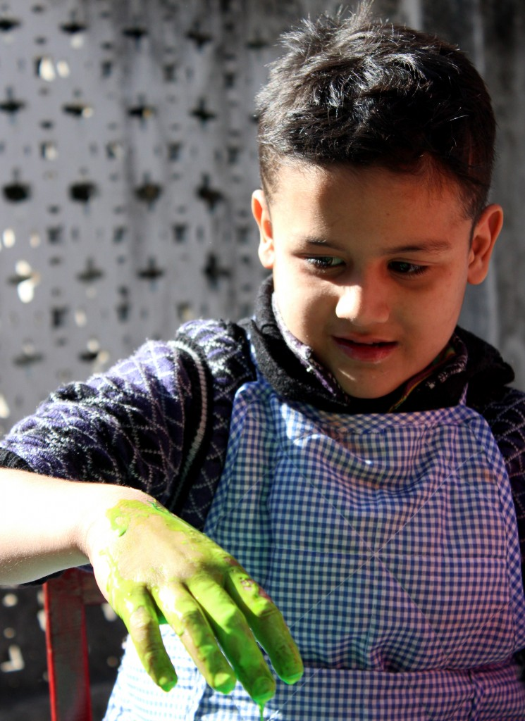 Little boy plays with green fingerpaint