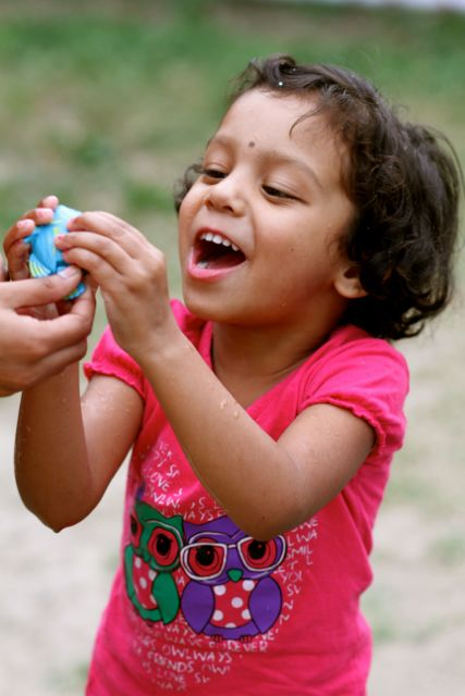 Little girl, very excited about holding a blue toy