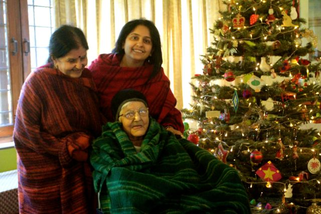 Elderly woman in wheelchair with daughter and granddaughter before a Christmas tree