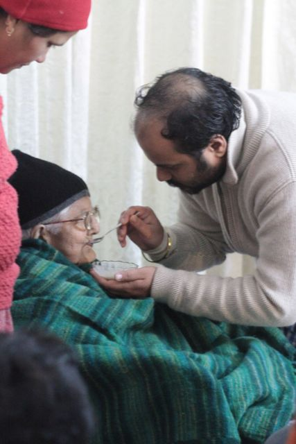 Young man feeds an elderly woman
