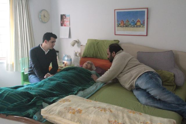 Elderly woman asleep in bed; two grown-up grandsons on either side