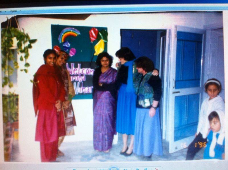 Group of women standing in front of a colorful bulletin board in a cschool