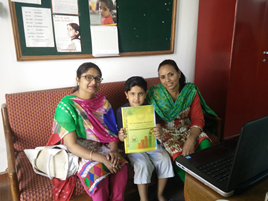 Little boy with Mom and teacher, holding report card