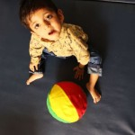 Little boy sitting on floor, looking up, with a ball