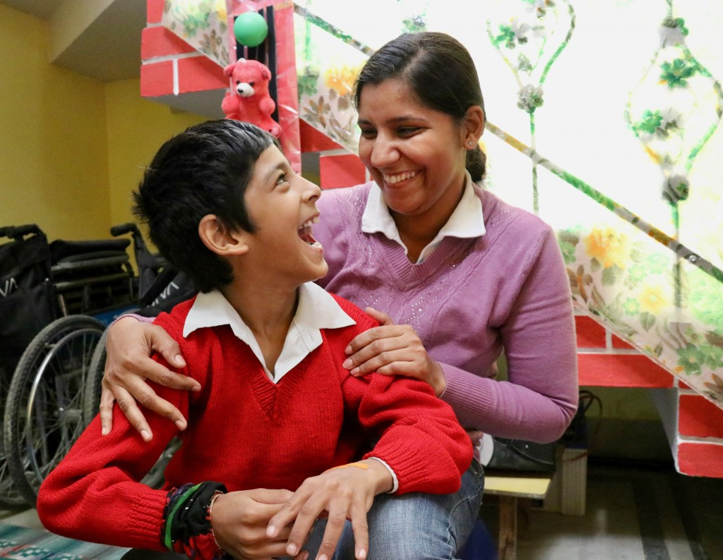 Boy with Derebral Palsy looking up at a woman - both are smiling broadly