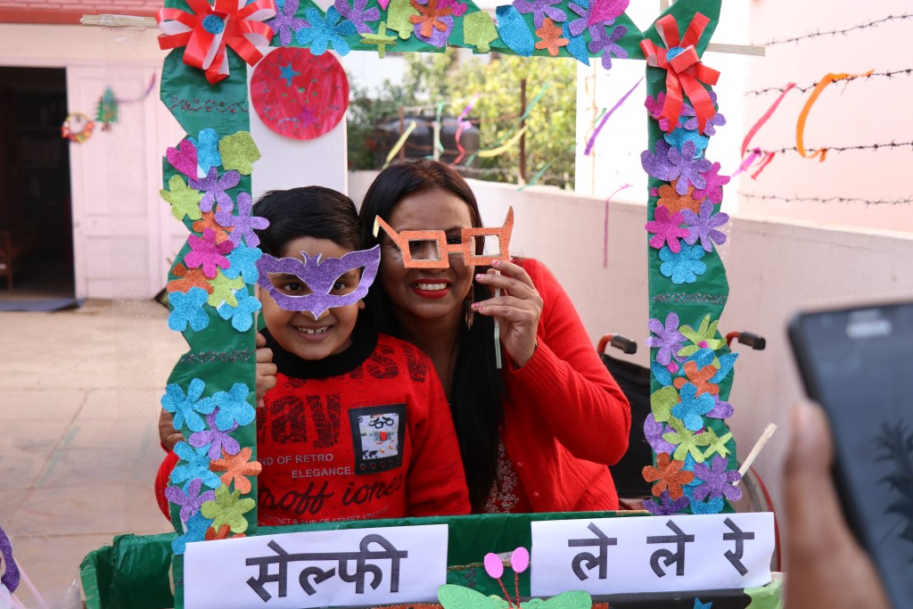Woman and child in a selfie booth, both smiling and holding up big fake spectacles
