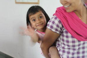 Little girl on a woman's back, waving happily