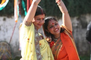 Two Bengali women - one in red sari, one in yellow, in a dance pose