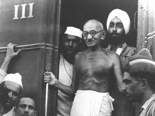 Gandhiji alighting from a train, man in Gandhi cap to his right; sardarji to his left