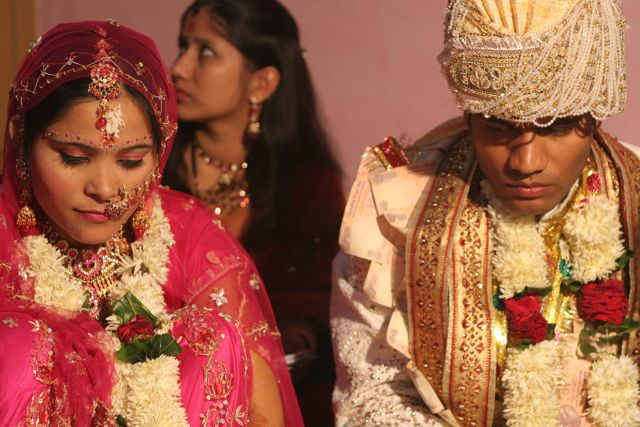 Young couple at their Hindu wedding. Bride in pink; groom in white, wearing a turban.