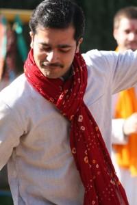 Man in white kurta, red scarf, dancing