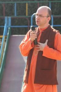 Dutch man in orange kurta, holding mike, singing