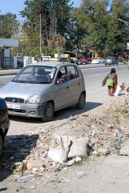 Car on the side of the road, rag-picker girl with a sack going past