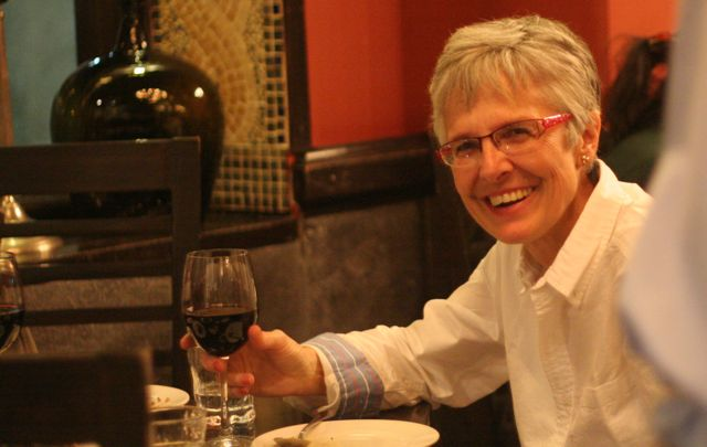 Author in a restaurant, holding a glass of wine, showing off hew haircut (stylish!)