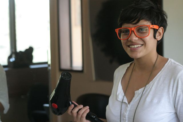Attractive hair stylist, holding hair dryer, wearing huge orange glasses