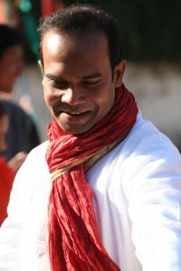 Handsome man in white kuta, red scarf