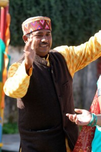 Garhwali man in yellow kurta and brown vest, dancing