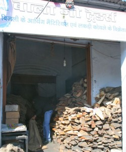 Huge woodpile - no space to move except for one guy in blue filling a sack with logs