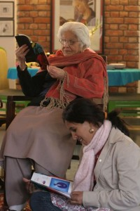 Young teacher sitting at the feet of elderly woman, both reading