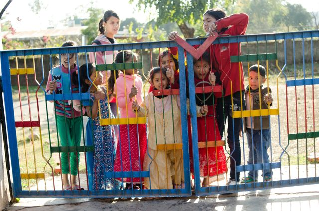 COlorfully dressed children eagerly opening the gate to Latika vihar
