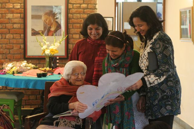 Three young teachers giving an elderly woman a huge birthday card