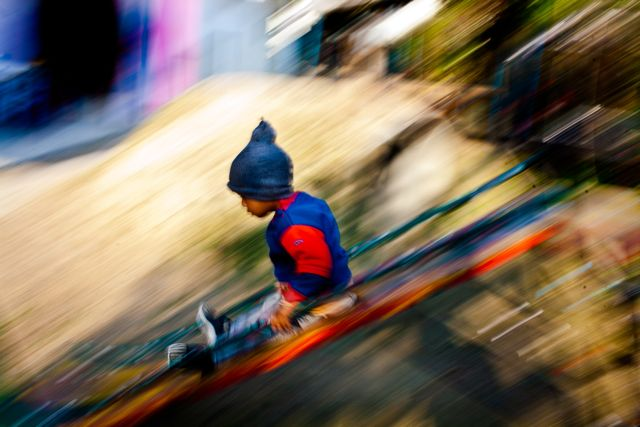 Child coming down a slide, background fabulously blurred