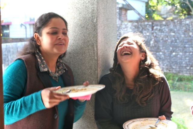Two women, backlit, one serious, one with head thrown bak, laughing