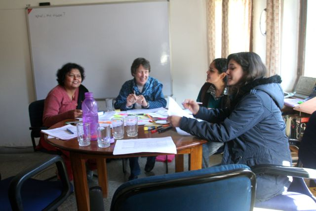 Four women around a round table, chart papers and colored pens strewn across it