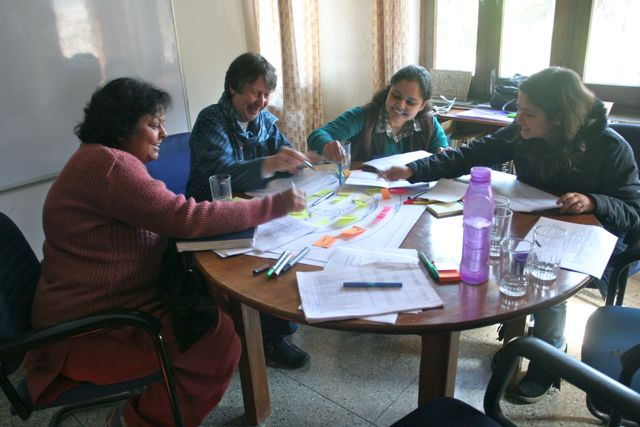 Women around the table which is covered with colored pens, post-its and posters, laughing and pointing at charts