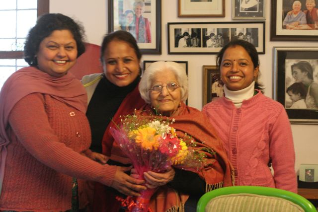 Elderly woman with three young teachers giving her a bouquet of flowers
