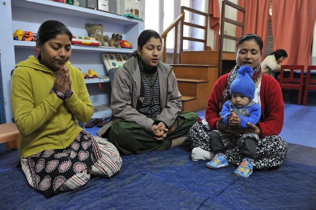 Three Indian women in prayer, seated on the floor, one holding a baby on her lap