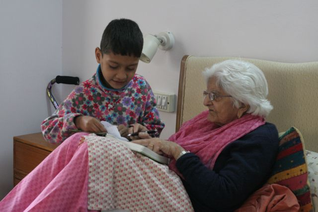 Little boy beside elderly woman in a bed, both poring over his schoolbooks
