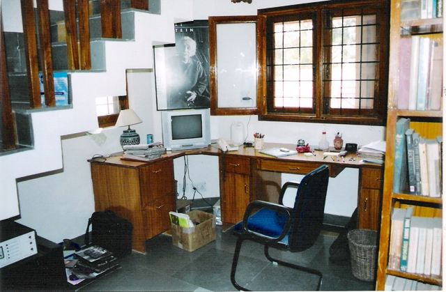 An L-shaped desk beneath a window, cluttered with papers and files.