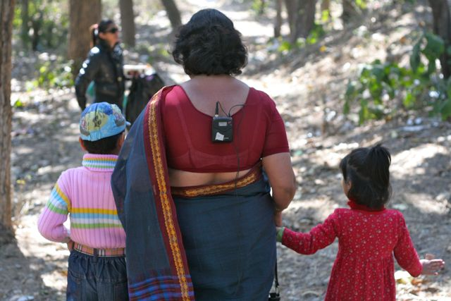 Picture of two children walking down a forest path with a woman in a sari who has a microphone tucked into the back of her sari blouse