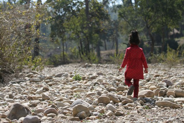 Little girl walking alone up a rough, rocky dry riverbed