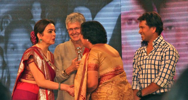 Manju and Jo on stage receiving award from Sachin Tandulkar and Nita Ambani