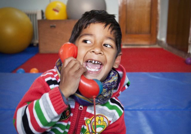 Very smiley little boy on the phone