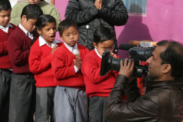 Kids saying prayer in morning assembly with camera man in foreground