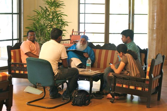 Ravi with a group of students, sitting around him in rapt attention