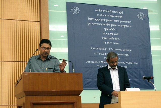 Man at podium, in background, sign announcing IIT Mumbai Distinguished Alumnus awards