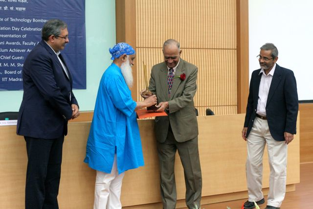 Ravi, long white beard, receives his award from the Chairman of the Board of Governors; two other men looking on