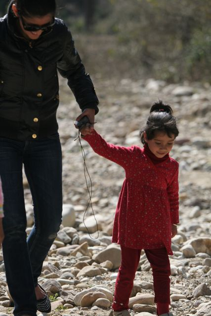 Little girl being led down a rough, rocky path