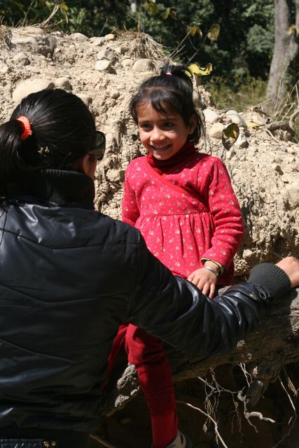 Filmmaker speaking to little girl in red, sitting on a tree branch