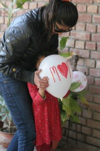 Little girl being shown how to place the balloon in front of her face