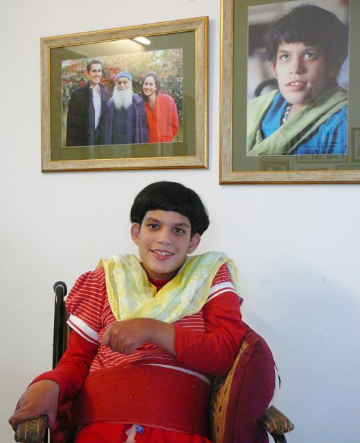 Moy smiling happily, sitting in her wheelchair. Behind on the wall, photos of her father, brother and sister