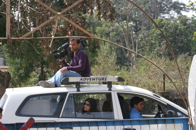 Camera man on roof of moving car, director giving instructions from open window in backseat