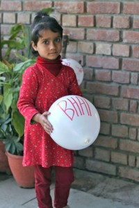 Little girl holding a balloon looking solemn and uncooperative